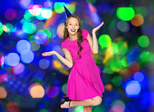 Happy young woman or teen girl in party cap Royalty Free Stock Image
