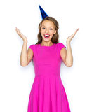 Happy young woman or teen girl in party cap. People, holidays, emotion, expression and celebration concept - happy young woman or teen girl in pink dress and Royalty Free Stock Images