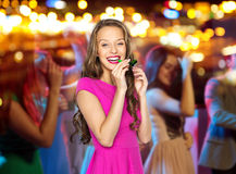 Happy young woman or teen girl with party horn. People, holidays and celebration concept - happy young women or teen girl in pink dress blowing to party horn at Royalty Free Stock Image