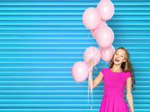 Happy young woman or teen girl in pink dress. People, holidays and fashion concept - happy young woman or teen girl in pink dress with helium air balloons over Stock Photo