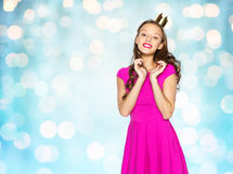 Happy young woman or teen girl in pink dress. People, holidays and fashion concept - happy young woman or teen girl in pink dress and princess crown over blue Royalty Free Stock Photos