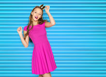 Happy young woman or teen girl in pink dress. People, holidays and fashion concept - happy young woman or teen girl in pink dress and princess crown over blue Stock Photos