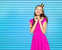 Happy young woman or teen girl in pink dress. People, holidays and fashion concept - happy young woman or teen girl in pink dress and princess crown over blue Stock Images