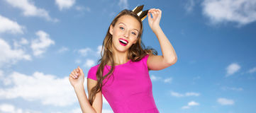 Happy young woman or teen girl in pink dress. People, holidays and fashion concept - happy young woman or teen girl in pink dress and princess crown over blue Royalty Free Stock Photo
