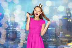 Happy young woman or teen girl in pink dress. People, holidays and fashion concept - happy young woman or teen girl in pink dress and princess crown over night Stock Photography