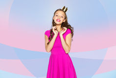 Happy young woman or teen girl in pink dress. People, holidays and fashion concept - happy young woman or teen girl in pink dress and princess crown over pink Stock Photos
