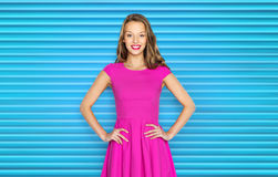 Happy young woman or teen girl in pink dress. People, style and fashion concept - happy young woman or teen girl in pink dress over blue ribbed background Royalty Free Stock Photo