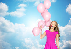 Happy young woman or teen girl in pink dress. Summer, people, holidays, birthday and fashion concept - happy young woman or teen girl in pink dress with helium Stock Photography