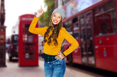 Happy young woman or teen girl pointing finger up Stock Image