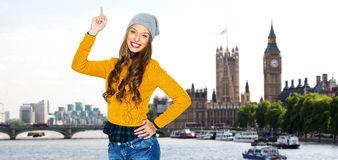 Happy young woman or teen girl pointing finger up Stock Photos
