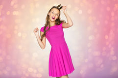 Happy young woman or teen girl in princess crown. People, holidays and fashion concept - happy young woman or teen girl in  dress and princess crown over rose Royalty Free Stock Photo