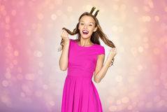 Happy young woman or teen girl in princess crown. People, holidays and fashion concept - happy young woman or teen girl in pink dress and princess crown over Stock Photography