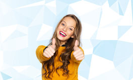 Happy young woman or teen girl showing thumbs up stock photos