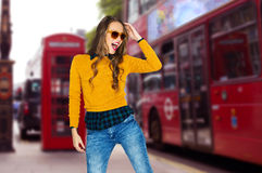 Happy young woman or teen over london city street. People, travel, tourism, style and fashion concept - happy young woman or teen girl in casual clothes and Royalty Free Stock Photos