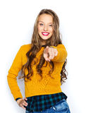 Happy young woman or teen pointing finger on you. People, style and fashion concept - happy young woman or teen girl in casual clothes pointing finger on you Royalty Free Stock Photos