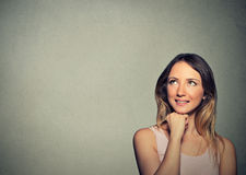Happy young woman thinking dreaming has ideas looking up Royalty Free Stock Images