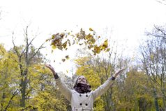 Young woman throwing autumn leaves Royalty Free Stock Photo