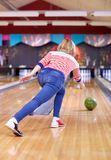 Happy young woman throwing ball in bowling club Royalty Free Stock Images