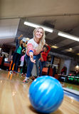 Happy young woman throwing ball in bowling club Royalty Free Stock Photo