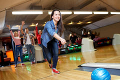 Happy young woman throwing ball in bowling club Royalty Free Stock Photography