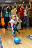 Happy young woman throwing ball in bowling club. People, leisure, sport and entertainment concept - happy young women throwing ball in bowling club Stock Photography