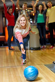 Happy young woman throwing ball in bowling club Stock Photography
