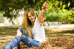 Happy young woman throwing leaves Stock Image