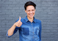 Happy young woman with thumbs up sign. Portrait of a happy young woman with thumbs up sign Royalty Free Stock Photos