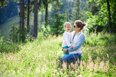 Happy young woman and toddler son on sunny meadow. Happy young women and toddler son on sunny meadow in mountains stock images