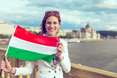 Woman stretching Hungarian flag outdoor at Budapest color graded. Happy young woman with toothy smile stretching Hungarian flag on Margaret bridge, near to stock images