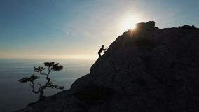 Epic Aerial view of a silhouette of a young woman climbing to the top of a mountain against the sea at sunset. Lady on