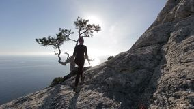 Young woman walking high in mountains above a sea. Lady on the summit in beautiful scenery observing Black sea from a. Happy young woman on top of mountain stock footage