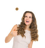 Happy young woman tossing coin. Isolated on white stock photography