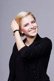 Happy young woman touching her hair Stock Photos