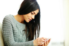 Happy young woman touching smartphone at home Royalty Free Stock Photos