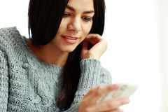Happy young woman touching smartphone Stock Photo
