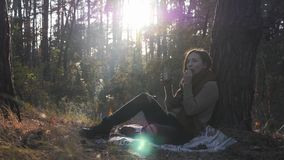 Happy young woman tourist drinking hot tea and eating cookies relaxing in autumn forest with sun rays. Female traveler enjoying th. E evening in fall forest stock footage