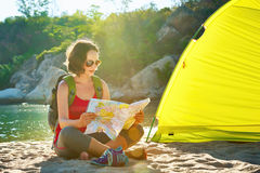 Happy young woman tourist nearby the tent looking into map Stock Images
