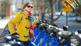 Happy young woman tourist ready to ride a rental bicycle in New York City at sunny spring day. Female traveler enjoying her time i stock images