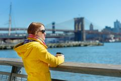 Happy young woman tourist sightseeing in New York City at sunny spring day. Female traveler drinking coffee in downtown Manhattan. royalty free stock photo