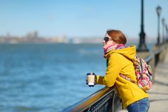 Happy young woman tourist sightseeing in New York City at sunny spring day. Female traveler drinking coffee in downtown Manhattan. royalty free stock image
