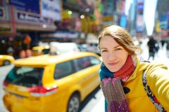 Happy young woman tourist sightseeing at Times Square in New York City. Female traveler enjoying view of downtown Manhattan. Happy young woman tourist royalty free stock photo