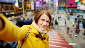 Happy young woman tourist sightseeing at Times Square in New York City. Female traveler enjoying view of downtown Manhattan. Happy young woman tourist stock photos