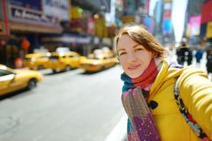 Happy young woman tourist sightseeing at Times Square in New York City. Female traveler enjoying view of downtown Manhattan. stock photos