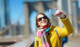Happy young woman tourist sightseeing at Brooklyn Bridge, New York City, at sunny spring day. Female traveler enjoying view of dow stock photos