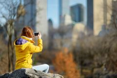 Happy young woman tourist taking pictures at Central Park in New York City. Female traveler enjoying views of downtown Manhattan. stock photography