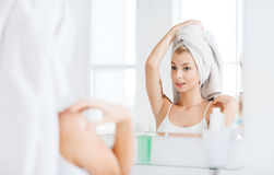Happy young woman with towel at mirror in bathroom. Beauty, hygiene, morning and people concept - smiling young woman with head wrapper in towel looking to stock image