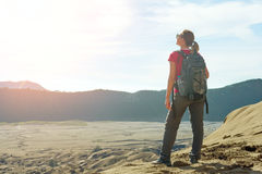 Happy young woman with a travel backpack enjoying sunrise at desert canyon. Young woman backpacker traveling along mountains, happy female walking discovering stock images