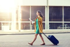 Happy young woman with travel bag and map in city. Travel, trip, tourism, people and vacation concept - happy young woman with carry-on travel bag and map Stock Images