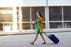 Happy young woman with travel bag and map in city. Travel, trip, tourism, people and vacation concept - happy young woman with carry-on travel bag and map Royalty Free Stock Photos